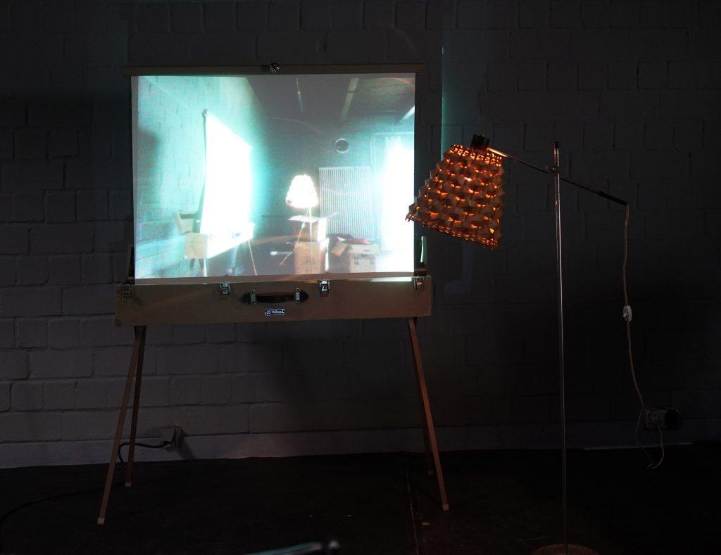 Eine alte Leinwand, daneben eine Lampe. Auf die Leinwand projeziert ist eine Abbildung von der gleichen Lampe und der gleichen Leinwand aus einer anderen Perspektive.